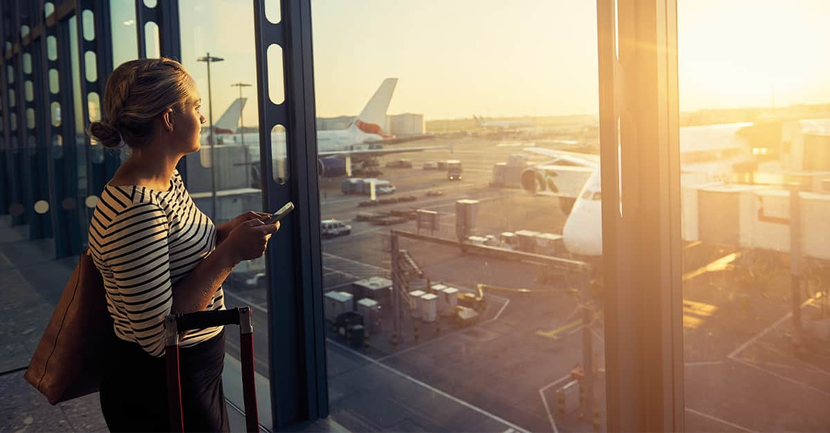 Woman looking out an airport window at an airplane